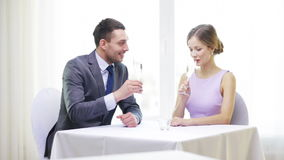 Couple with glasses of champagne at restaurant. Restaurant, couple and holiday concept - smiling man with glass of champagne looking at his wife or girlfriend at stock video