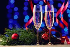 Couple of glasses with champagne on a wooden table with Christma. A couple of glasses with champagne on a wooden table with Christmas red balls, a glossy ribbon Royalty Free Stock Images