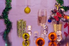 A couple of glasses with champagne on a wooden table with Christmas red balls, a glossy ribbon with a sprig of spruce on the backg Royalty Free Stock Photos