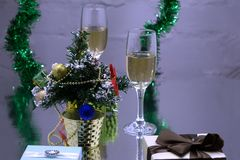 A couple of glasses with champagne on a wooden table with Christmas red balls, a glossy ribbon with a sprig of spruce on the backg Stock Images