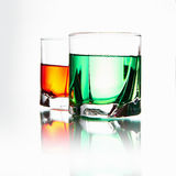 Couple glasses with cocktail. Still life with glasses with alcohol.absinthe against whiskey royalty free stock photography
