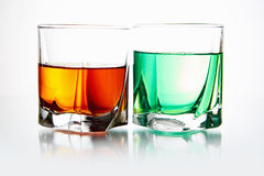 Couple glasses with cocktail. Still life with glasses with alcohol.absinthe against whiskey stock photos