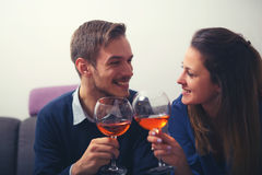 Couple with glasses of red wine clinking their glasses i Royalty Free Stock Images