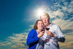 Couple with glasses of wine embraces Stock Images
