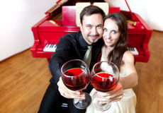 Couple with glasses of wine near piano Stock Photography