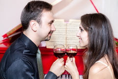 Couple with glasses of wine near piano Royalty Free Stock Photography