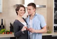 Couple with goblets embraces one another Royalty Free Stock Image