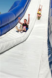 Couple Goes Down Giant Slide In Obstacle Race Challenge Royalty Free Stock Image