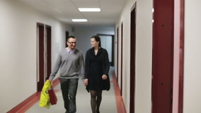 The couple goes a long corridor. Young man with glasses and a beautiful woman is holding hands stock video footage