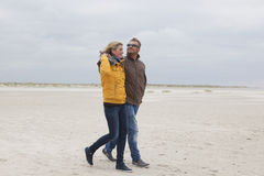 Couple goes on a sandy beach in autumn Stock Photos