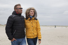 Couple goes for a walk on the beach in autumn Royalty Free Stock Photo