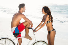 Couple going on a bike ride on the beach Stock Images