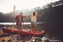 Couple going for a canoe ride in the lake. Young men helping women to step into the kayak. Couple going for a canoe ride in the lake Stock Image