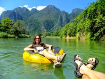 Couple going down Nam Song River in a tube surrounded by karst s. Cenery in Vang Vieng, Laos. Tubing is a popular tourist activity in Vang Vieng royalty free stock images