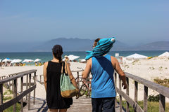 Couple going to the beach. View of a couple going to the beach on sunny day and clear sea water. The man carries an umbrella and woman a beach bag. Photo made in Stock Photography