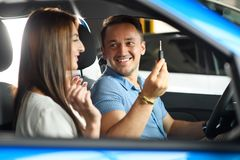 Couple is going to buy new car. He is holding key from car in hand. They are both happy royalty free stock photography