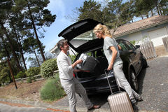 Couple going for a trip. Couple putting suitcases in car trunk for a journey Stock Image