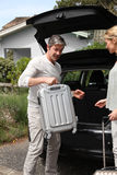 Couple going for a trip. Couple putting suitcases in car trunk for a journey Royalty Free Stock Photos