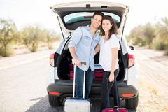 Couple going on vacation by car. Loving young caucasian couple standing with luggage and open car boot, getting ready for their road trip Stock Photos
