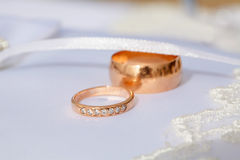 Couple of gold wedding diamond rings on wedding pillow Stock Image