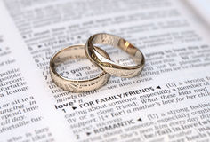 Couple of gold wedding rings on a dictionary page Royalty Free Stock Images