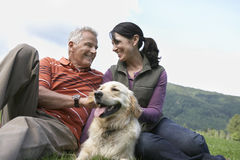 Couple With Golden Retriever On Grass Stock Photo