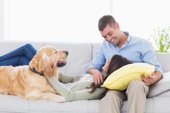 Couple with Golden Retriever on sofa Stock Photo