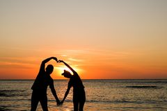 Couple at golden sunset at beach stock images