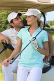 Couple in golf buggy. Couple in buggy in golf course Royalty Free Stock Image