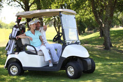 Couple in golf buggy Royalty Free Stock Images