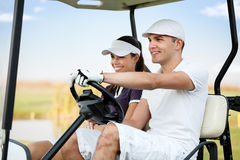 Couple in golf car. Happy young couple driving in golf cart Royalty Free Stock Images