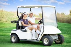 Couple in golf car. Young couple driving golf cart Stock Photography