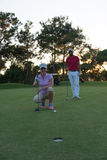 Couple on golf course at sunset Stock Image