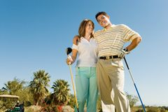 Couple of golfers embracing on golf course Royalty Free Stock Photos