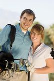Couple of golfers embracing on golf course Royalty Free Stock Image