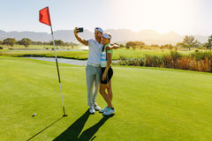 Couple of golfers making selfie at golf course. Young couple taking self portrait on putting green at golf course. Male and female golfers taking selfie with stock photography