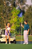 Couple Golfing 1. Couple Golfing, on green putting Royalty Free Stock Photography