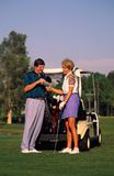 Couple Golfing. By golf cart with scorecard royalty free stock photo