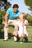 Couple Golfing On Golf Course. Lining Up Putt On Green royalty free stock images
