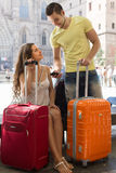 Couple with GPS navigator and baggage. Happy smiling young couple in shorts with GPS navigator and baggage outdoor Stock Photos
