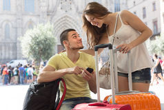 Couple with GPS navigator and baggage. Happy young couple in shorts with GPS navigator and baggage outdoor Stock Images