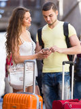 Couple with GPS navigator and baggage. Smiling tourists couple with GPS navigator and baggage in the street Stock Photos