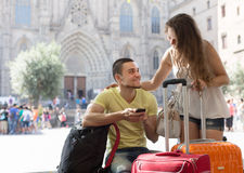 Couple with GPS navigator and baggage. Smiling young couple in shorts with GPS navigator and baggage outdoor Stock Photos