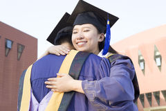 A couple of graduates. A couple of asian graduates are holding closely in campus very happily Stock Photography