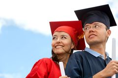 Couple of graduates outdoors Stock Image