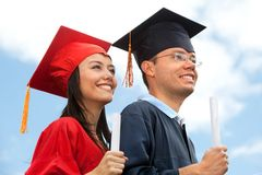 Couple of graduates outdoors Royalty Free Stock Photos