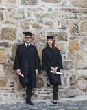 Couple in the Graduation Day. Young couple in the graduation day posing together near a rocky wall Royalty Free Stock Photo