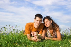 Couple in grass. Young couple lie on the grass Royalty Free Stock Image