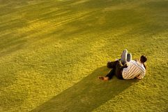Couple on Grass. Relaxing as the sun sets Stock Images