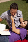 Couple on grass with book feeding grape Royalty Free Stock Photography